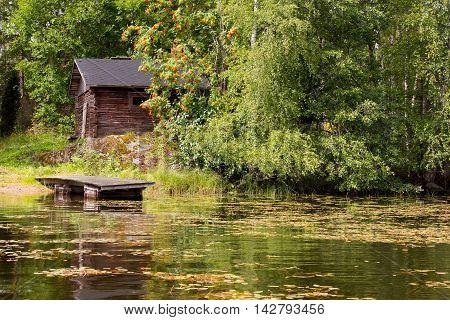 An old lakeside sauna hidden behind vegetation