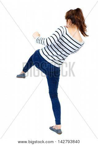 back view of woman funny fights waving his arms and legs. Rear view people collection. backside view of person.  Isolated over white background. Girl in a striped sweater makes striking out
