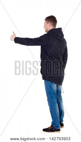 Back view of  man in jacket shows thumbs up.   Rear view people collection.  backside view of person.  Isolated over white background. Man in warm jacket standing left side showing the thumbs up.