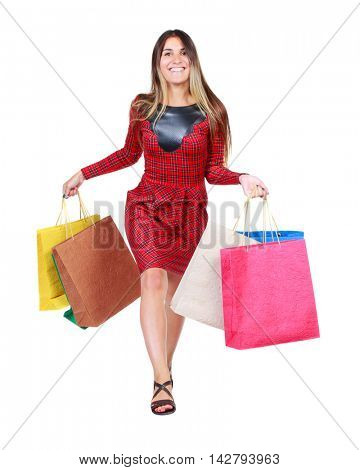 front view of a woman jumping with shopping bags. beautiful brunette girl in motion.  front view of person.  Isolated over white background. The girl in red plaid dress runs to meet us smiling and