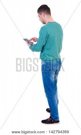 back view of business man uses mobile phone.    rear view people collection. Isolated over white background. backside view of person. A man in a green jacket and jeans standing cancer and working on