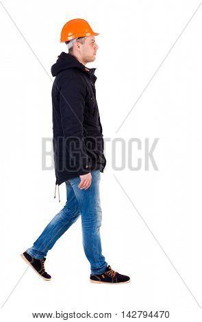 Back view of walking engineer in helmet.  Rear view people collection. Backside view of person. Isolated over white background. Engineer in warm clothes right away.