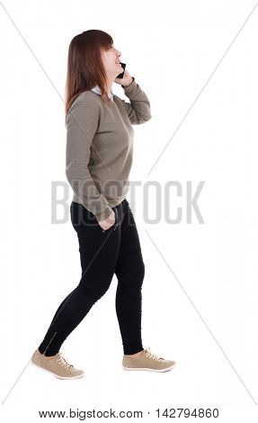 side view of a woman walking with a mobile phone. back view of girl in motion.  backside view of person.  Rear view people collection. Isolated over white background. Laughing girl with a phone in his