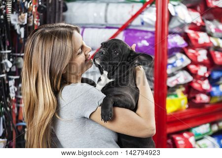 Happy Woman Carrying French Bulldog At Store
