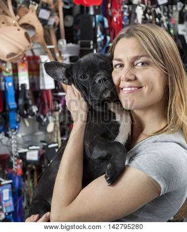 Loving Woman Embracing French Bulldog In Store