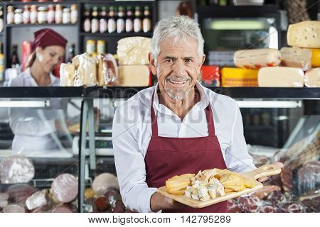 Smiling Salesman Holding Various Cheese On Board In Store