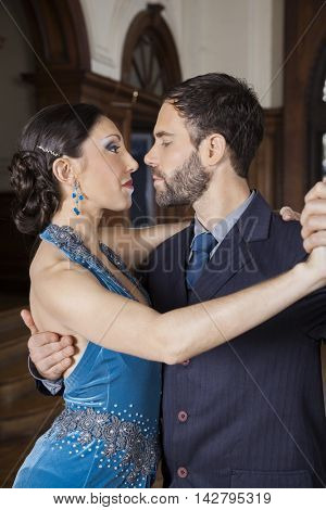 Mid Adult Dancers Performing Tango In Cafe