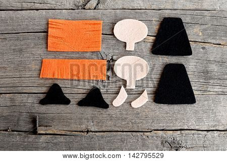 Cut felt parts for sewing witch toy. How to sew a Halloween witch ornament. Halloween crafts idea. Simple tutorial for kids and beginners. Step. Top view. Old wooden background
