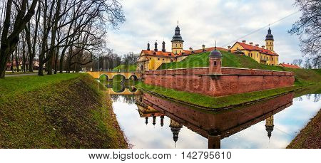 Walls of Nesvizh Castle in Belarus in winter. Beautiful nature with water and trees. Popular landmark