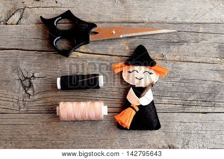 Halloween felt witch with broom, beige and black thread, needle, scissors on old wooden background. Simple Halloween ornament crafts for kids. Sewing idea. Tutorial. Step. Top view