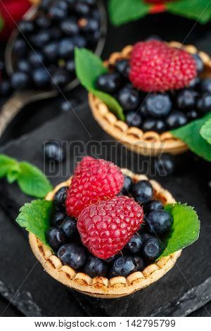 Tartlets with blueberries, raspberries and mint leafs on a black slate background