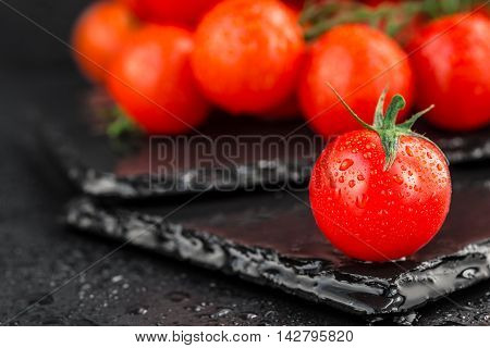 Fresh cherry tomatoes with water drops on slate backgound