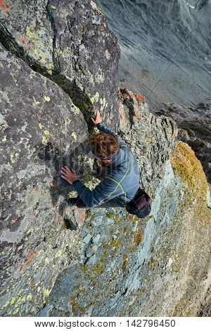 Hiker photographer climbs on the cliff in Alps. Switzerland, Trek near Matterhorn mount.