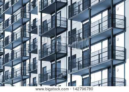Blue colorized construction background picture of modern apartment building with balconies