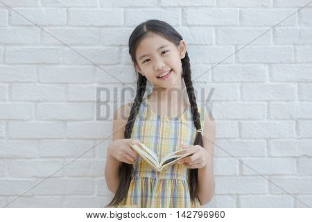 Asian girl reading story book on white brick wall