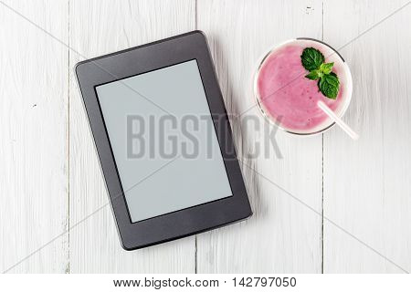 Berry smoothie with yogurt and ebook. Top view