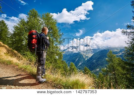 hiker in the Alps mountains. Trek near Matterhorn mount. hiker stands on the trail, looks at the valley, and drinks water from the H2O system
