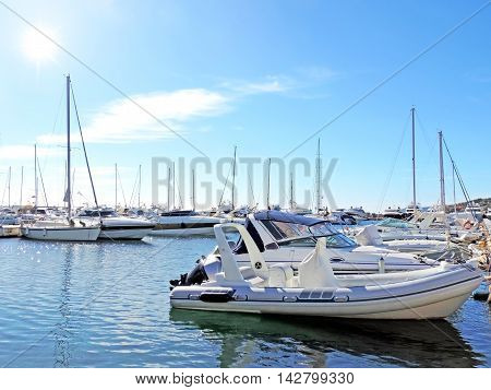 Yacht harbor with anchored luxury boats and sailing ships.