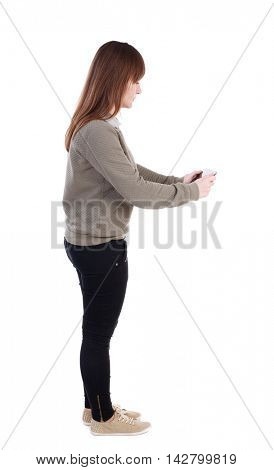 back view of standing young beautiful  woman  using a mobile phone. girl  watching. Rear view people collection.  backside view of person.  Isolated over white background. A girl in a gray jacket