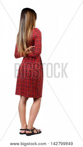 back view of standing young beautiful  woman.  girl  watching. Rear view people collection.  backside view of person. The girl in red plaid dress standing sideways with his arms crossed behind his