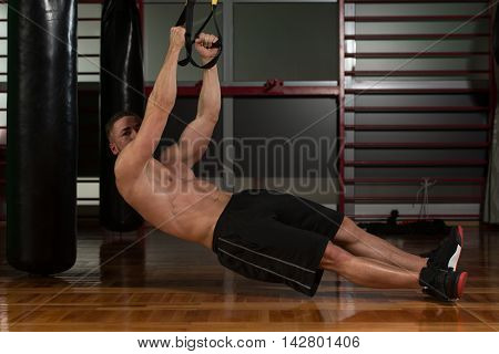 Young Attractive Man Training With Trx Fitness Straps