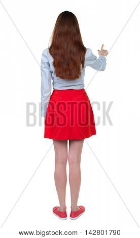 back view of woman. Young woman presses down on something. Isolated over white background. Rear view people collection. backside view of person. Long-haired brunette in red skirt finger presses the