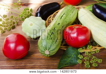 Red Tomato green cucumber fennel squash on a wooden table