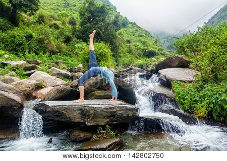 Yoga outdooors - woman doing yoga asana eka pada urdva dhanurasana Upward Bow Pose back benkd outdoors at waterfall in Himalayas