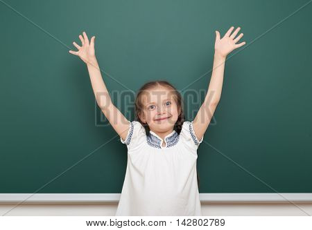 school student girl open arms at the clean blackboard, grimacing and emotions, dressed in a black suit, education concept, studio photo