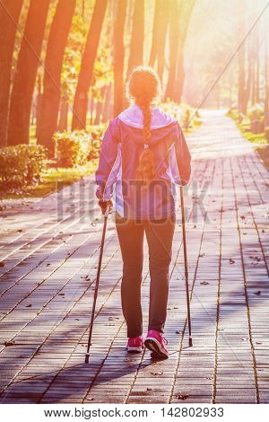 Nordic walking adventure and exercising concept - woman hiking with nordic walking poles in park. With lens flare and light leak