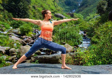 Yoga outdoors - sporty fit woman doing Ashtanga Vinyasa Yoga asana Virabhadrasana 2 Warrior pose posture at tropical waterfall