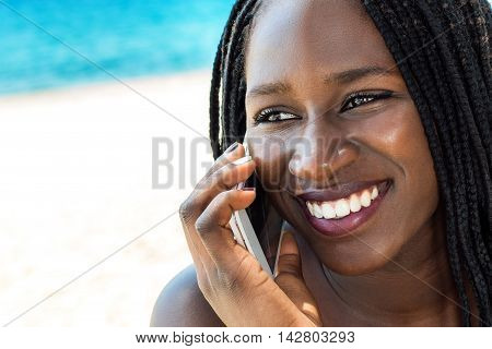 Close up face shot of attractive african teen girl talking on smart phone outdoors.