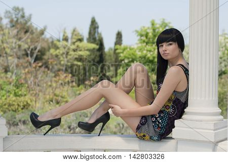 girl sits on columns in the Park