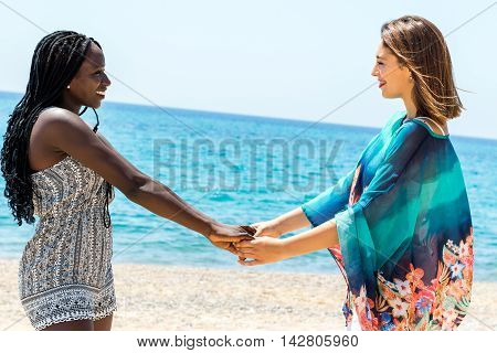 Close up portrait of two diverse teen girls holding hands on beach.