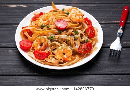 Pasta with shrimps and tomatoes close up