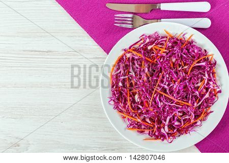 Salad coleslaw - red cabbage with carrots on white dish with fork and knife on table mat authentic classic recipe view from above