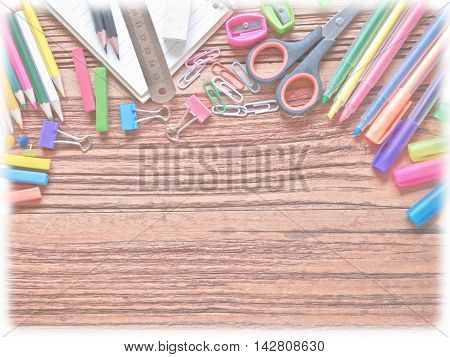 School and office supplies on wood background.(used white vignett)