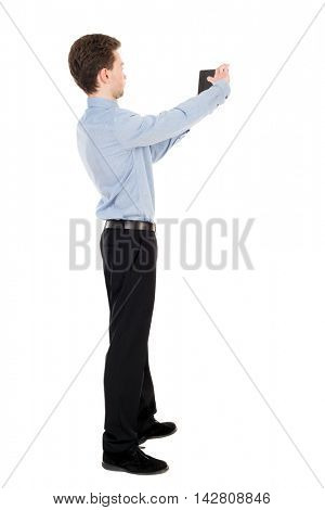 back view of standing business man photographing a phone or tablet. Rear view people collection.  backside view of person.  Isolated over white background. The curly-haired businessman in light shirt