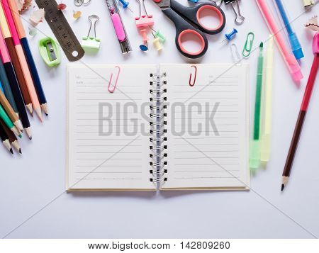 Top view notebook and office supplies on white background