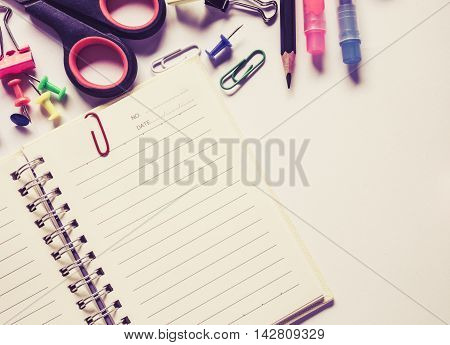 Top view notebook and office suplies on wood table made soft focus style