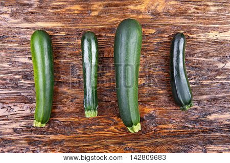 four fresh zucchini on a natural brown wooden background. Zucchini are vertical.