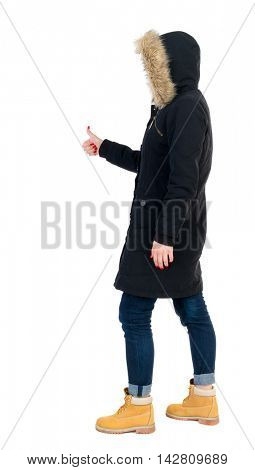 Back view of  woman thumbs up. Rear view people collection. backside view of person. Isolated over white background. The girl in warm winter jacket is black with cancer and shows thumb up.
