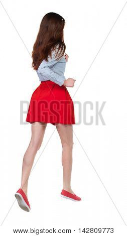 side view of running  woman. beautiful girl in motion. backside view of person.  Rear view people collection. Isolated over white background. Long-haired brunette in red skirt high jumps.