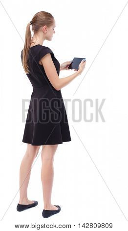back view of standing young beautiful  woman  and using a mobile phone. girl  watching. Rear view people collection.  backside view of person.  Isolated over white background. Blonde in a short black