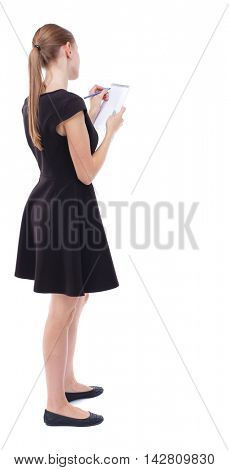 back view of  stands woman takes notes in a notebook. girl  watching. Rear view people collection.  backside view of person.  Isolated over white background. Blonde in a short black dress takes notes