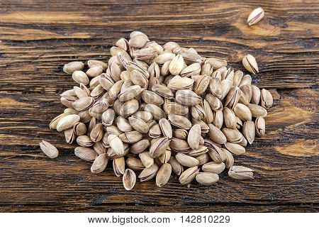 pistachios are scattered on a wooden background top view. healthy food nutritious and healthy product.