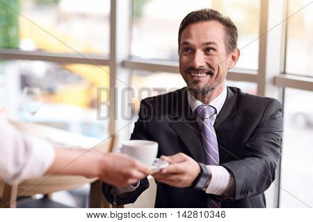 Thank you. Positive delighted man sitting at the table and getting cup of coffee from the waiter while resting in the cafe