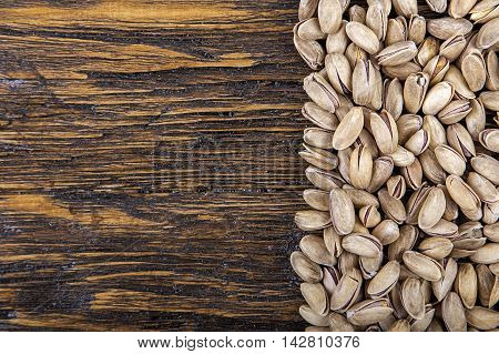 pistachios are scattered on a wooden background top view space for text. healthy food nutritious and healthy product.