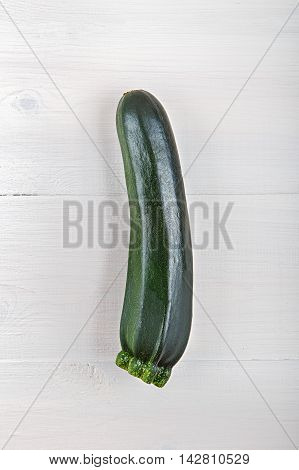 a fresh zucchini on a white wooden background. Zucchini is vertical.