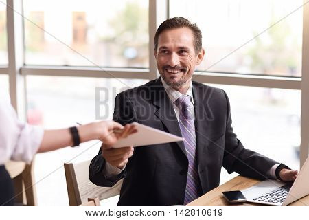 Here you are. Joyful content senior businessman sitting at the table and getting papers while expressing gladness